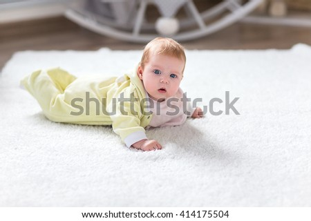 The baby lies on the floor on a white carpet in the nursery. - stock photo