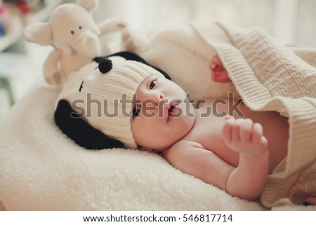 The baby lies wrapped in a knitted blanket. Smiles. Child knit beanie. Newborn smiling mother and surprised. On a white background