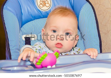 The baby sitting in highchair at home with toy