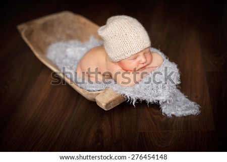 The baby sleeps in a trough with a blanket - stock photo