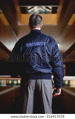 the back of a security guard who have in his hand a portable wireless transceiver with a blurry building on background - stock photo