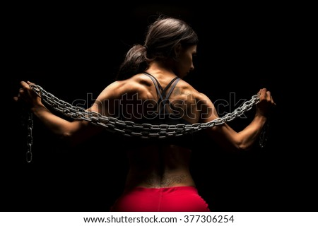 The back of a woman in a sports bra and red shorts with tattoos and a chain across her neck. - stock photo