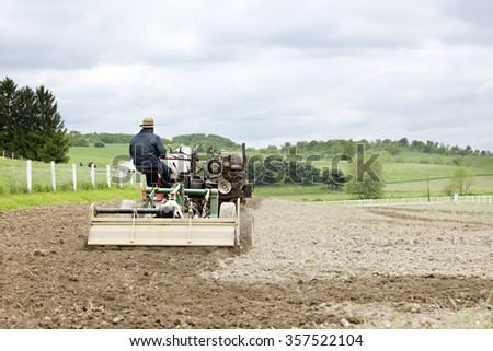 The back of an Amish on a horse-drawn cultivator on an overcast spring day. - stock photo