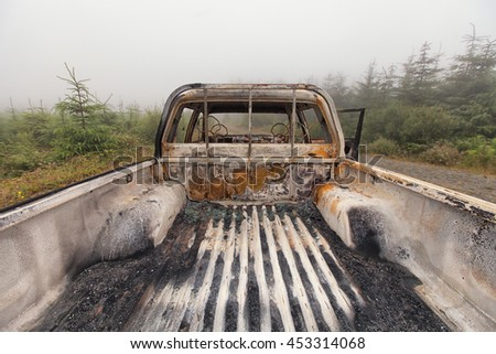 The back open cab of a burnt out pick up truck left abandoned on common ground.