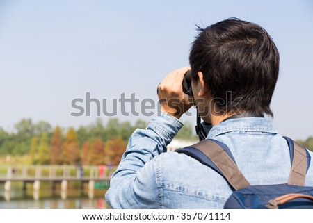 The back rear of man using binoculars - stock photo