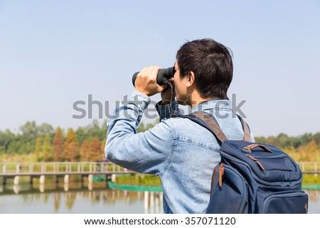 The back rear of man using binoculars for birdwatching - stock photo