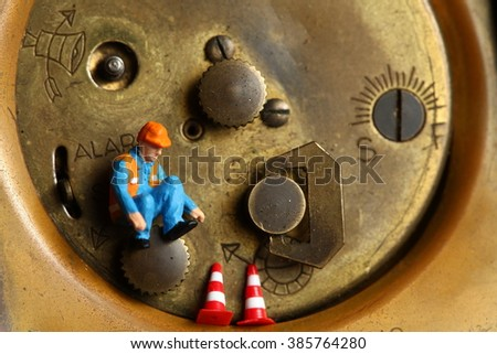 The back side of old and dirty brass table clock and miniature maintenance figure plastic model represent the clock service and time concept related idea.