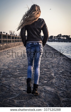 The back view of a girl walking down the village street in the wind, autumn - stock photo