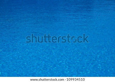 The background of pure water in the swimming pool of blue color - stock photo