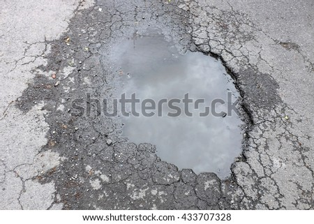 The bad asphalted road for cars with a big pothole filled with water - stock photo