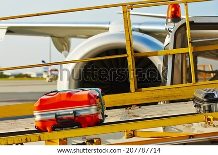 The baggage on the conveyor belt to the airplane - stock photo