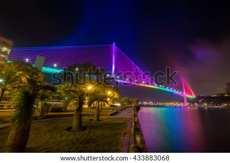 The Bai Chay Bridge in Ha Long, Vietnam lit up with colorful lighting at night.