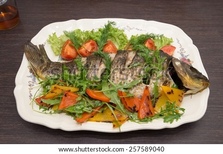The baked carp with vegetables and spices - stock photo