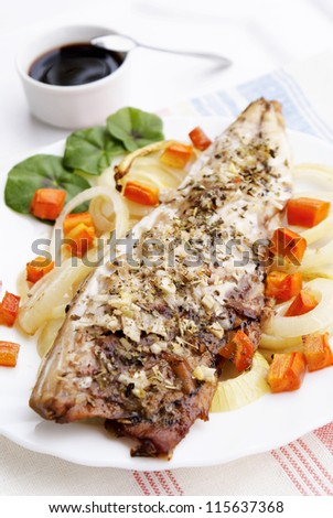 The baked fish with fried carrots and onion