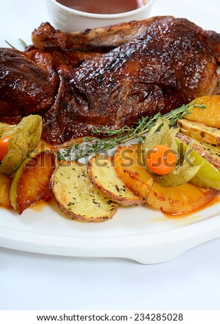 The baked half of duck with a potato, apples and pineapple - stock photo