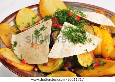 The baked meat with vegetables on a metal plate - stock photo