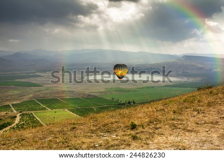 The balloon is flying over the Valley near the village of Koktebel in Crimea against the backdrop of the dramatic sky with a rainbow - stock photo