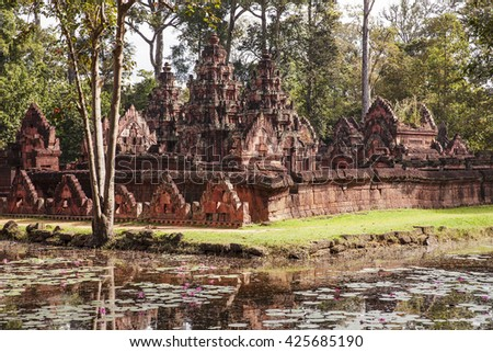 The Banteay Srei temple is one of the oldest temples in the Angkor Wat area of Cambodia. As viewed from the outside over a pond, the well-preserved building was made of a reddish stone.
