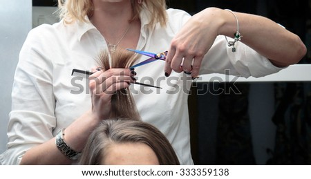 The barber cuts her hair with scissors