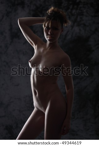 The bared girl against a dark background - stock photo