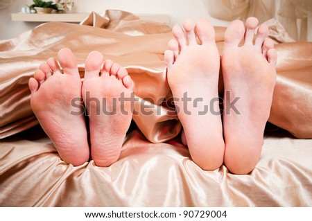 The bared heels of pair in stick out from under bed-sheets - stock photo