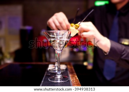 The bartender decorates stemware with martini.
