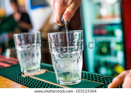 The bartender mixes a summer cocktail at the bar - stock photo