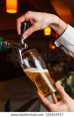 the bartender pours beer into a glass from the tap