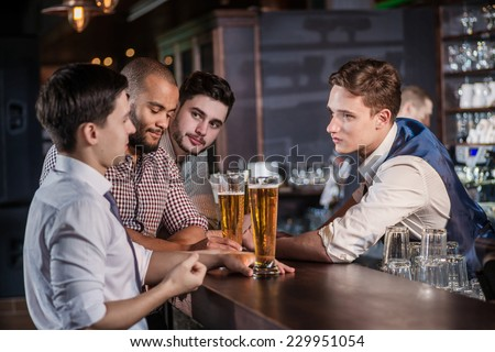 The bartender takes orders for beer. Three cheerful friend makes ordering a beer from the bartender at the bar - stock photo