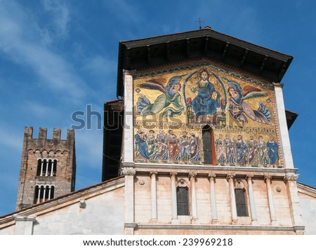 The Basilica di San Frediano in Lucca is a medieval basilica with large campanile and a 13th-century mosaics on its facade. The church is situated against the blue sky background. - stock photo