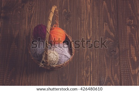 The basket of different clews of threads are on the wood table - stock photo