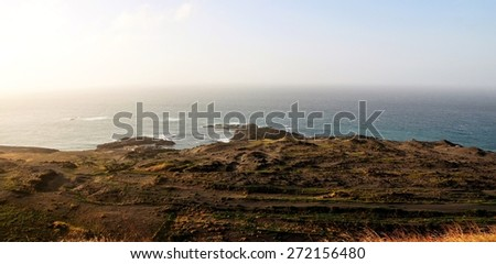 The bay of Salinas on the town of Sao Jorge with its surrounding black sand dunes  sits below the cliff with its volcanic peninsula extending into the ocean - stock photo