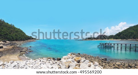 the beach and rocky shore with wooden walkway to a speedboat
