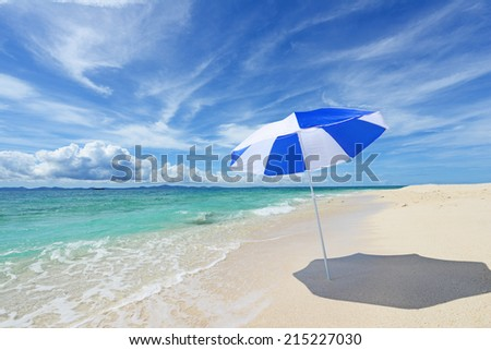 The beach and the beach umbrella of midsummer. - stock photo