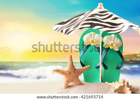 The beach and the beach umbrella. Starfish and flip flops on the sandy beach  at ocean background - stock photo