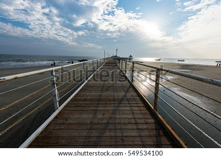 The beach and the bridge in the background of the blue sky white clouds