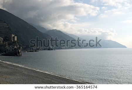 The beach at Monterosso al mare. Water, mountains and storm clouds. Cinque Terre. Italy - stock photo
