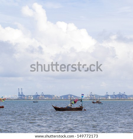 The beach with a blue sky and clouds , The sea, with boats parke