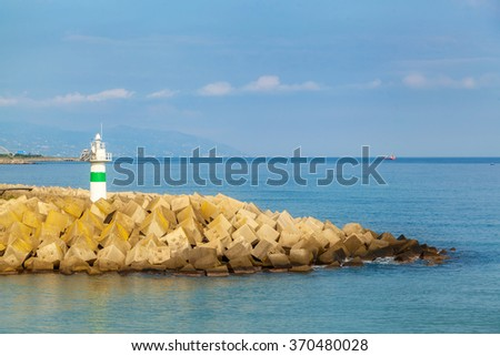 the beacon costs on an artificial embankment from stones by the sea - stock photo