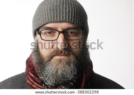 The bearded and strict man in a red scarf glasses and winter cap. Portrait on a white background. - stock photo