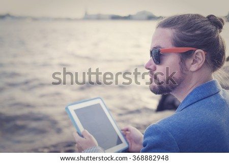 The bearded hipster photographer in a blue jacket on the tablet running on the banks of the Neva River in St. Petersburg. - stock photo