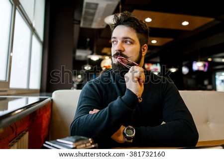 the bearded young man sitting in a cafe and looks thoughtfully out the window