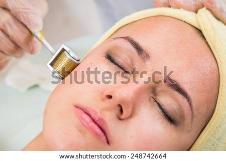 The Beautician and the client in the spa salon. Conducting anti-aging treatments. Revitalization, injection therapy, mikronidling. Medical treatments for the face. - stock photo