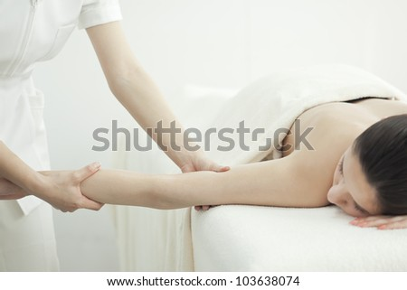 The beautician who massages the arm - stock photo