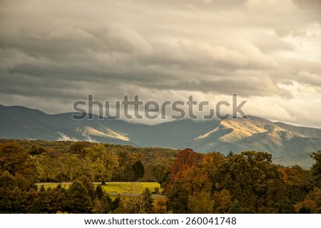 The beautifful Appalachian mountains in West Virginia  during autumn colors as the sun highlitghs the clouds. - stock photo