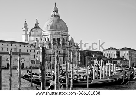 The beautiful and famous tourist destination the Basilica Santa Maria della Salute church with venetian gondolas in sunny weather on the Grand Canal, Venice, Italy, black and white image - stock photo