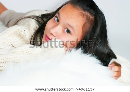 The beautiful Asian girl in a knitted sweater