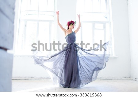 The beautiful ballerina dancing in long gray dress on white room background - stock photo