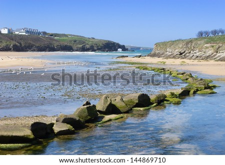 The beautiful beach at Porth, near Newquay, Cornwall, UK. The boulders mark where the river flows into the sea. Copyspace available. - stock photo