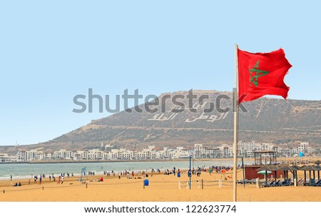 The beautiful beach in Agadir with flag of Morocco - stock photo